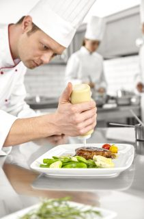 Male chef preparing steak plate